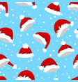 seamless pattern with santa hats and snow on blue vector image vector image