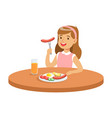 cute girl eating sausage while having breakfast in vector image