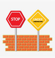 under construction and stop signs with bricks wall vector image vector image
