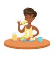 cute boy having breakfast in the kitchen colorful