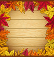 Border from autumn leaves on wooden background