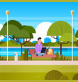 young man sitting on bench in park using laptop vector image