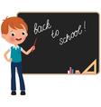 Schoolboy standing at the blackboard vector image