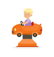 cute blonde little boy riding on an orange car vector image vector image