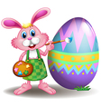 A rabbit painting the easter egg vector image