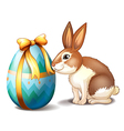A rabbit and an Easter egg with a ribbon vector image vector image