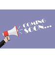 Hand holding megaphone with word Coming soon vector image vector image