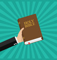 hand holding holy bible vector image vector image