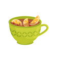 green cup of tea with red cranberry and slices of vector image vector image