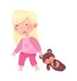 sleepy little girl in pajamas pulling teddy bear
