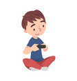 cute boy sitting on floor playing video game vector image vector image