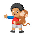 a little boy holding a funny monkey vector image vector image