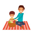 father with her son sitting on blanket with food vector image