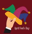 april fools day hand holding hat joker vector image vector image