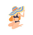 girl in black swimsuit and hat sitting on beach vector image vector image