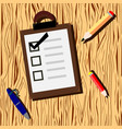 wooden background with checklist and pencil vector image