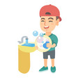 little caucasian boy washing dishes in the sink vector image