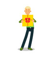 young smiling blonde man standing with yellow gift vector image vector image