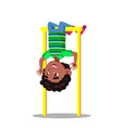 sporty little boy hanging on horizontal bar upside