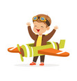 cute little boy in pilot costume playing toy plane vector image