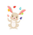 cute cartoon bunny juggling with colored eggs vector image