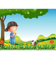 A boy under tree with his pet vector image