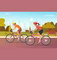 cyclists male and female rides at the urban park vector image vector image