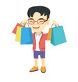 happy asian boy holding shopping bags vector image vector image