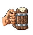 male hand holding full beer wooden mug with foam vector image vector image