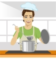 Young chef wearing cooking at stove vector image