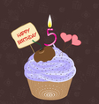 Birthday cupcake with lit candle in shape of