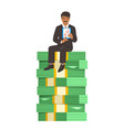 Successful businessman sitting on a stack of money