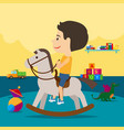 boy riding toy horse in kindergarten vector image