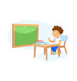 happy kid school boy sitting at desk in classroom vector image