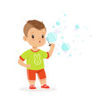 cute little boy playing with bubble blower vector image vector image