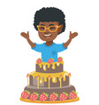 little african boy jumping out of a large cake vector image vector image