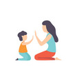 mother playing patty cake with her son mom and vector image vector image
