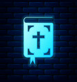 glowing neon bible book icon isolated on brick vector image vector image