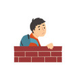 teen boy with backpack standing behind brick wall vector image vector image