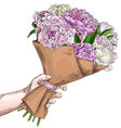 hand holding lush peonies bouquet wrapped in craft vector image vector image