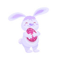 cute fluffy pink bunny with a painted easter egg vector image