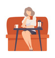 woman sits on a red sofa at a table in a cafe vector image vector image