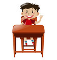boy at desk having one hand up vector image