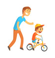 father teaching his son to ride a bicycle vector image vector image