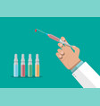 ampoules and syringe in hand vector image