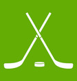 crossed hockey sticks and puck icon green vector image vector image