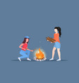 women hikers making fire couple girls holding vector image vector image