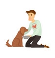volunteer in sweater with heart feeds homeless dog vector image
