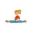 sweet redhead little girl in warm clothing playing vector image vector image