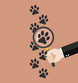hand holding magnifying glass over paw print vector image vector image